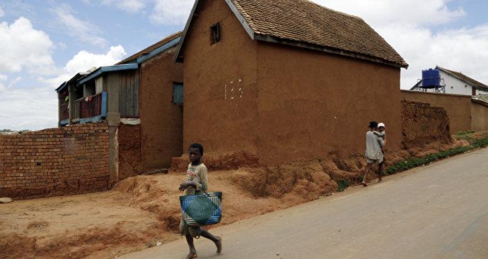 A young girl runs past a house in Antananarivo, Madagascar