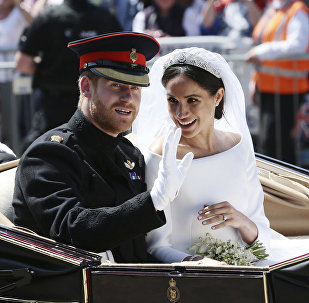 Britain's Prince Harry and Meghan Markle ride in an open-topped carriage after their wedding ceremony at St. George's Chapel in Windsor Castle in Windsor, near London, England, Saturday, May 19, 2018