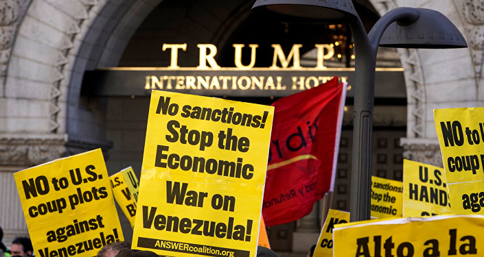 Activists hold up signs during a Hands Off Venezuela as they march past the Trump International Hotel in Washington, U.S., March 16, 2019