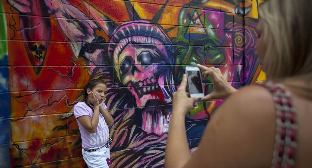 In this March 19, 2015 file photo, a girl poses for a picture in front of a mural depicting the statue of liberty as death, at Bolivar square in Caracas, Venezuela