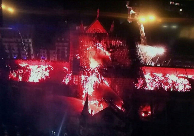 An image taken from a television screen shows an aerial view of the Notre-Dame Cathedral engulfed in flames on April 15, 2019, in the French capital Paris