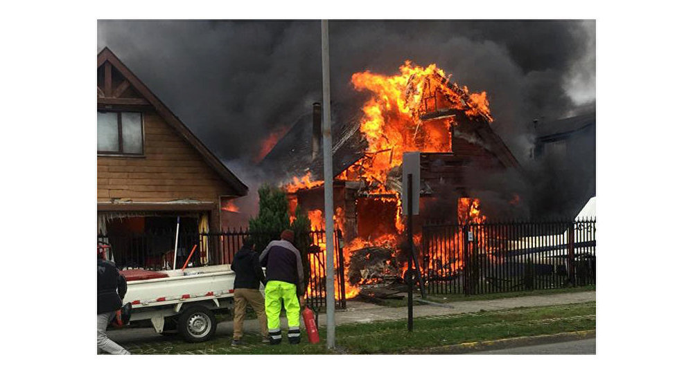 A house wrapped in flames is seen after a plane crashed and exploded in Puerto Montt, Chile, April 16, 2019.