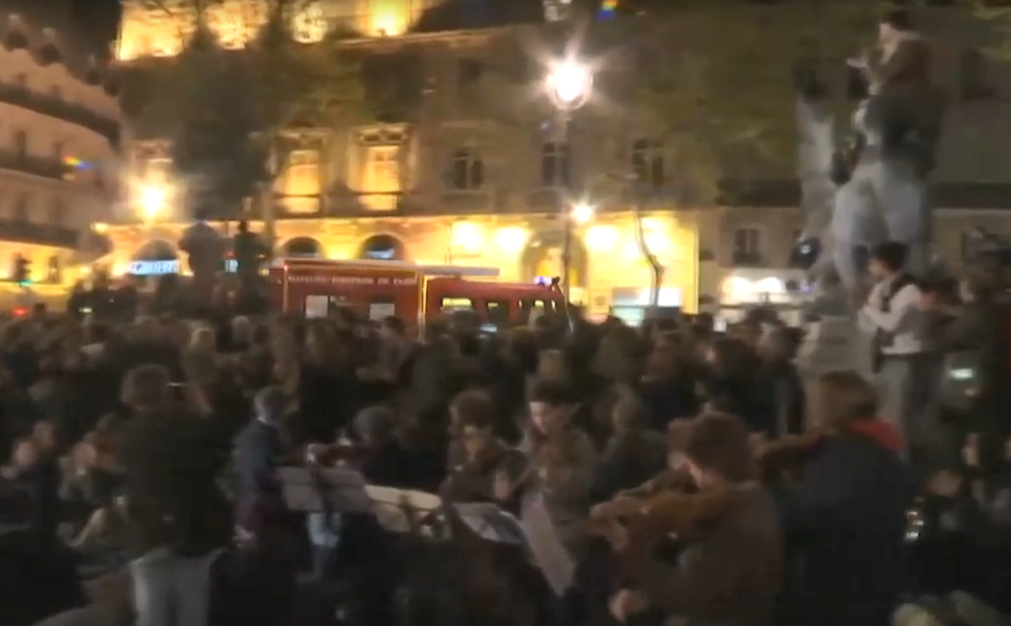 A fire truck passing the Notre Dame vigil in Paris is greeted with cheers
