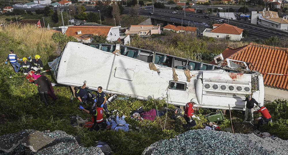 Rescue officials attend the scene after a tour bus crashed in Canico on Portugal's Madeira Island, Wednesday, April 17, 2019.