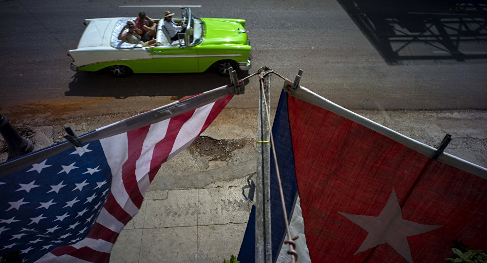 A U.S., and a Cuban national flag, hang from a balcony to mark the restored full diplomatic relations between Cuba and the Unites States, in Old Havana, Monday, July 20, 2015