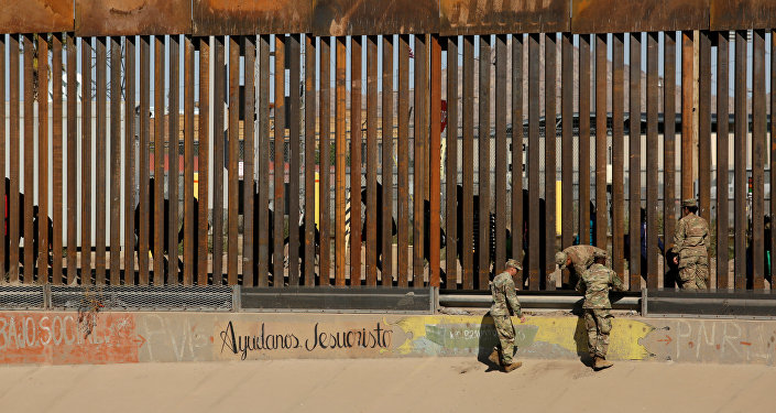 U.S. soldiers walk next to the border fence between Mexico and the United States, as migrants are seen walking behind the fence, after crossing illegally into the U.S. to turn themselves in, in El Paso, Texas, U.S., in this picture taken from Ciudad Juarez, Mexico, April 3, 2019