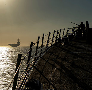 Sailors stand watch on the brow of the Arleigh Burke-class guided-missile destroyer USS Bainbridge while the ship follows the Nimitz-class aircraft carrier USS Abraham Lincoln into the Strait of Gibraltar in the Atlantic Ocean, April 13, 2019. Picture taken on April 13, 2019
