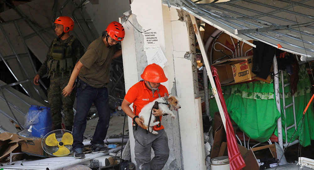 A rescuer carries a search dog as they try to reach survivors at a collapsed four-storey building following an earthquake in Porac town, Pampanga province, Philippines, April 23, 2019.