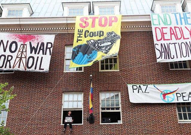 An activist in opposition of the U.S. involvement in Venezuela occupying the Venezuelan Embassy, sits in a window sill in Washington, U.S., April 25, 2019.