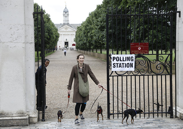 A woman brings her dogs to a polling station in London in 2018