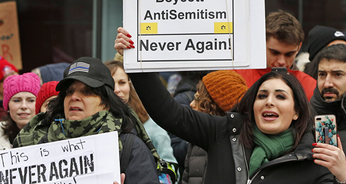 Political activist Laura Loomer, right, holds a sign across the street from a rally organized by Women's March NYC after she barged onto the stage interrupting Women's March NYC director Agunda Okeyo who was speaking during a rally in Lower Manhattan, Saturday, Jan. 19, 2019, in New York. Loomer was escorted off the stage after the incident