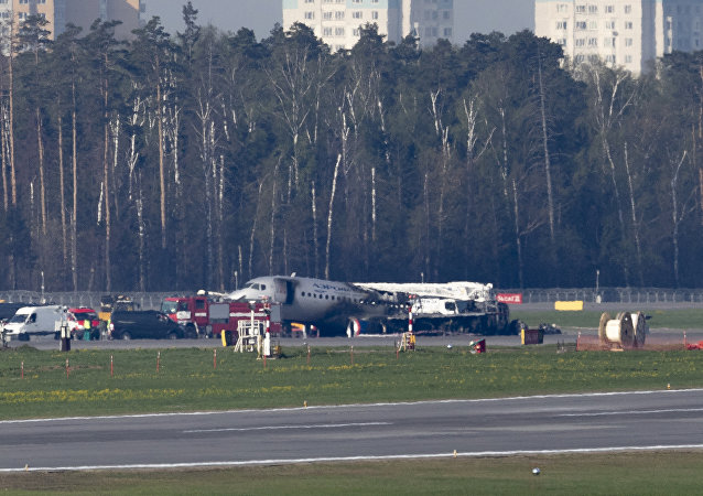 The Sukhoi SSJ100 aircraft of Aeroflot Airlines, center in the background, is seen after an emergency landing in Sheremetyevo airport outside Moscow, Russia, Monday, May 6, 2019