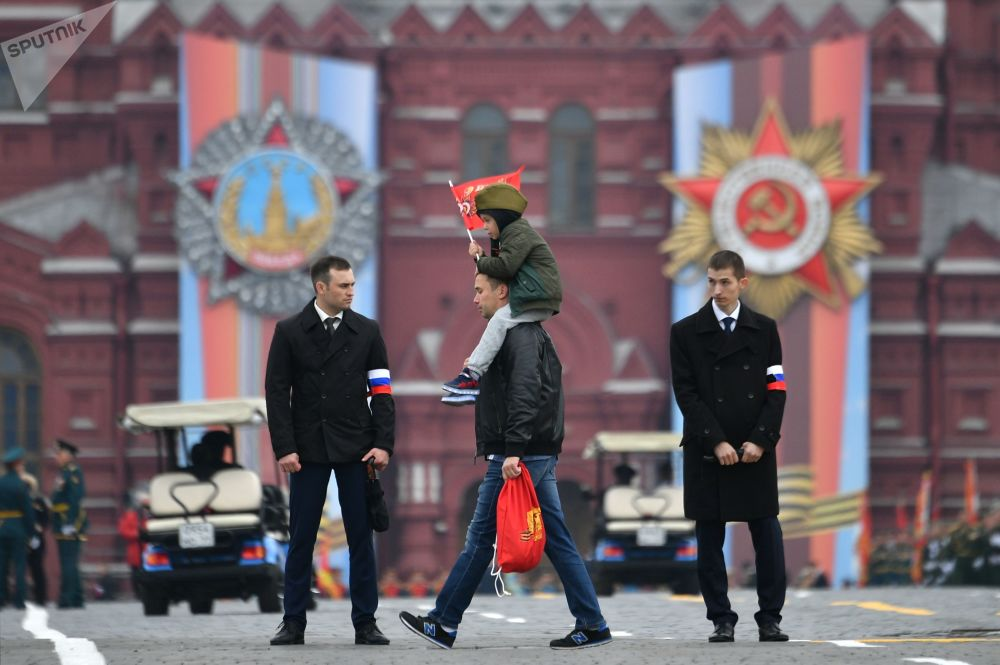 A Man Carrying a Child Before the Victory Day Parade at the Red Square in Moscow