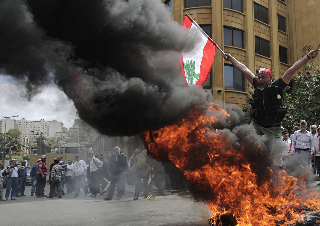 A Lebanese retired soldier holds a Lebanese national flag as he jump over burning tires during a protest in front of the government building during a cabinet meeting to discuss an austerity budget, in Beirut, Lebanon