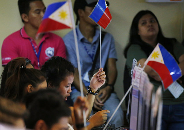 Volunteers of an election watchdog wave Philippine flags to seek assistance during the unofficial tally of votes at Monday's midterm elections Tuesday