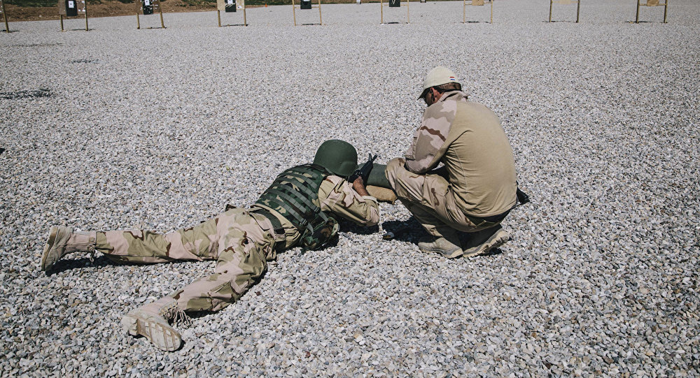 A Dutch army trainer helps a Kurdish Peshmerga soldier during a military training session in Iraq