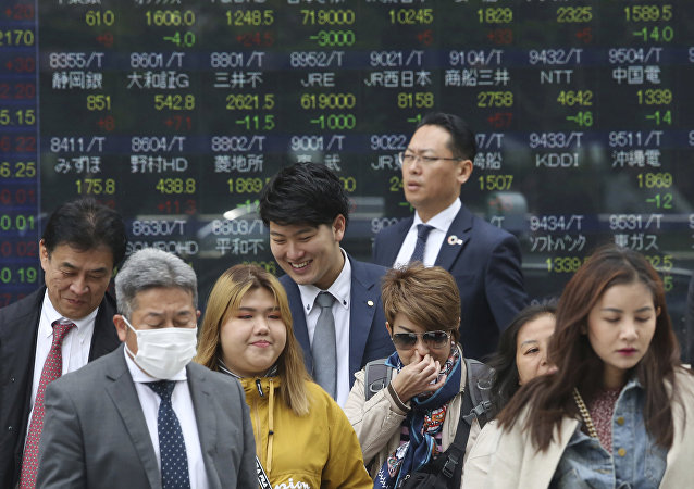 People stand in front of an electronic stock board of a securities firm in Tokyo, Wednesday, April 17, 2019.
