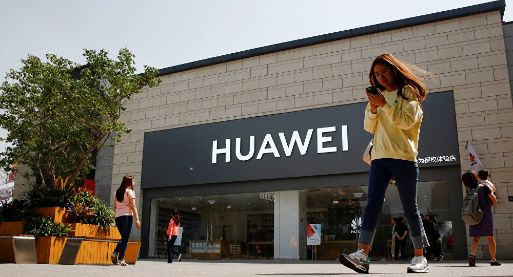 A woman looks at her phone as she walks past a Huawei shop in Beijing, China May 16, 2019