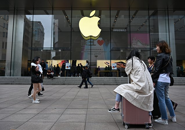 People walk past the front of an Apple store in central Shanghai on May 8, 2019
