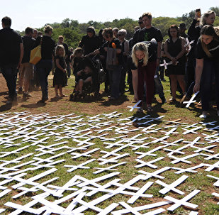 People place white crosses, representing farmers killed in the country, at a ceremony at the Vorrtrekker Monument in Pretoria