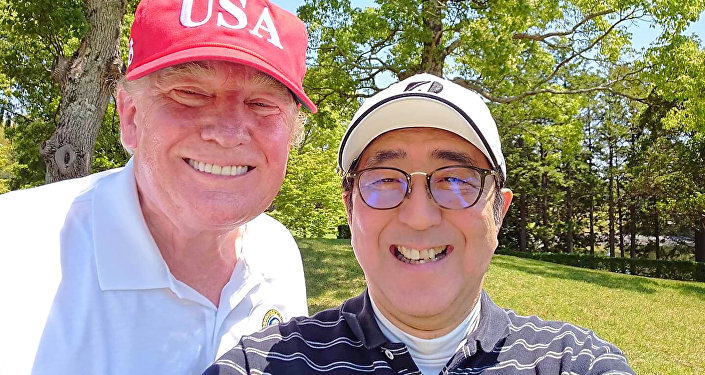 This handout photo taken from the twitter account of The Prime Minister's Office of Japan on May 26, 2019 shows US President Donald Trump (L) and Japan's Prime Minister Shinzo Abe (R) posing for a photograph while playing a round of golf at Mobara Country Club in Chiba.  Handout / The Prime Minister's Office of Japan