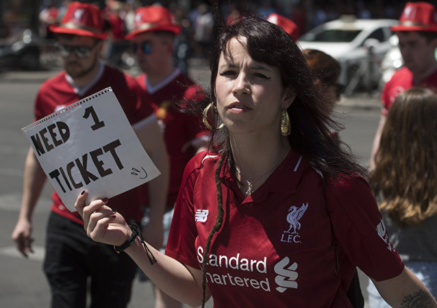 A Liverpool supporter holds a placard reading Need 1 ticket in Madrid on June 1, 2019 before the UEFA Champions League final football match between Liverpool and Tottenham Hotspur