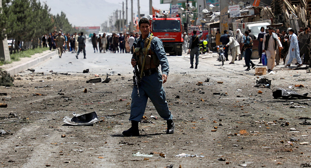 An Afghan policeman stands guard at the site of a suicide attack while others remove a wreckage of a car hit in the attack in Kabul, Afghanistan May 31, 2019.