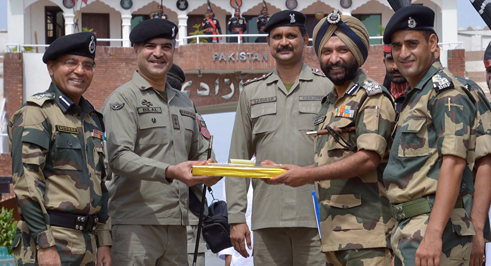 Pakistani Wing Commander Bilal (C) presents sweets to Indian Border Security Force (BSF) Deputy Inspector General JS Oberoi (2R) on the occasion of the Eid al-Fitr festival which marks the end of the holy month of Ramadan, at the India Pakistan Wagah Border Post, about 35 kms from Amritsar on July 6, 2016
