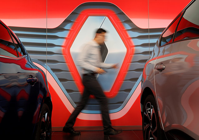 An employee walks in front of the logo of Renault carmaker at a dealership in Reze near Nantes