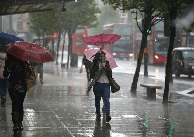 A woman's umbrella blown inside-out as she walks through a heavy rain shower on Oxford Street in London (File)