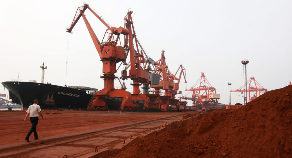 Bulldozer scoop soil containing various rare earth to be loaded on to a ship at a port in Lianyungang, east China's Jiangsu province on September 5, 2010
