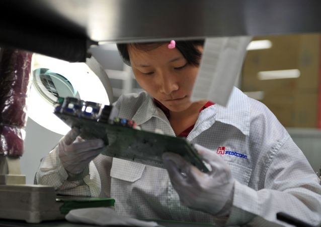 A worker inspects a motherboard on a factory line at the Foxconn plant in Shenzen on May 26, 2010