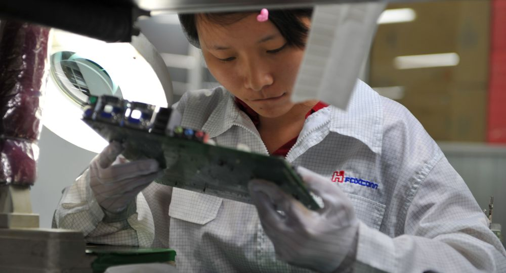 A worker inspects a motherboard on a factory line at the Foxconn plant in Shenzen on 26 May 2010