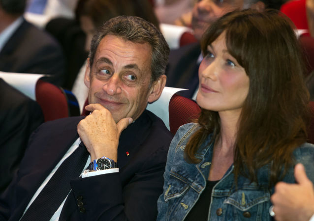 Former French President and candidate for the right-wing Les Republicains (LR) party primaries ahead of the 2017 presidential election Nicolas Sarkozy (L) and his wife Carla Bruni look on during a meeting in Toulon, southeastern France, on October 21, 2016.