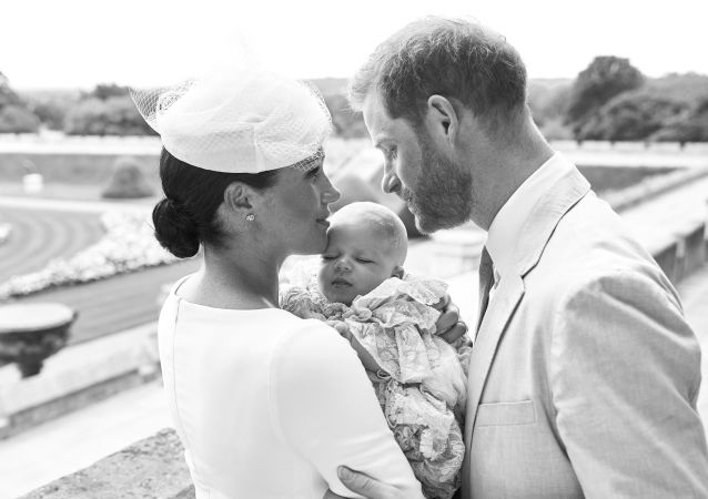 This official christening photograph released by the Duke and Duchess of Sussex shows Prince Harry, Duke of Sussex and Meghan, Duchess of Sussex with their son, Archie Harrison Mountbatten-Windsor at Windsor Castle with with the Rose Garden in the background, near London 6 July 2019