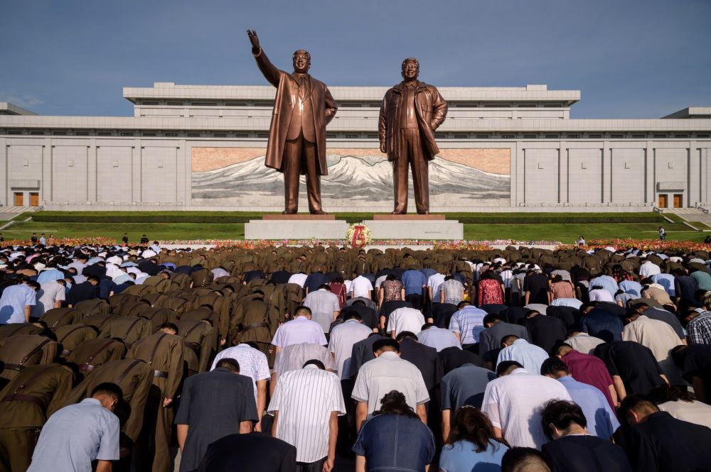 People bow before the statues of the late North Korean leaders Kim Il Sung and Kim Jong Il as the country marks the 25th death anniversary of Kim Il Sung, at Mansu Hill in Pyongyang on July 8, 2019.