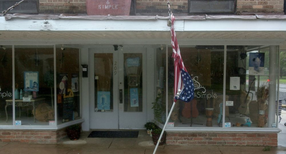 A torn U.S. Flag dangles from a store front in Morgan City, Louisiana ahead of Tropical Storm Barry Saturday, July 13,2019. - Tropical Storm Barry is the first tropical storm system of 2019 to make landfall in the United States and could dump up to two feet of rain along with strong winds and storm-surge flooding according to weather reports. (Photo by Seth HERALD / AFP)