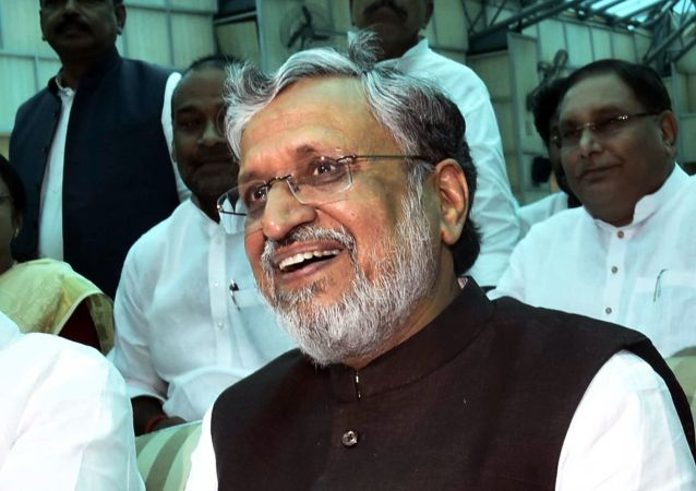 Deputy Chief Minister Sushil Kumar Modi share a light moment after oath taking ceremony at Raj Bhawan in Patna, India, Thursday, July 27, 2017