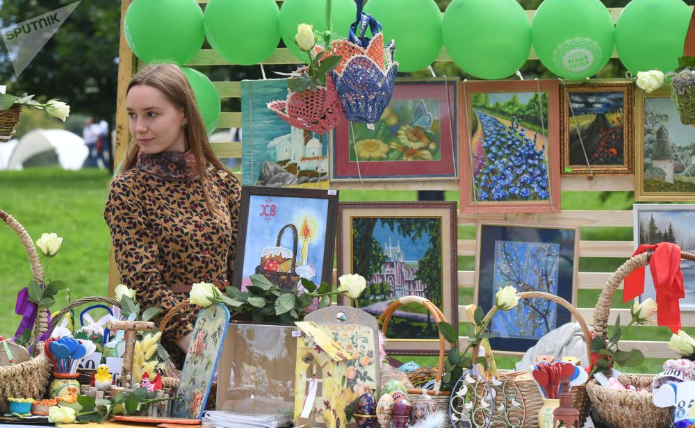 A woman sells pieces of art at the Russian Field festival of Slavic art in Moscow.