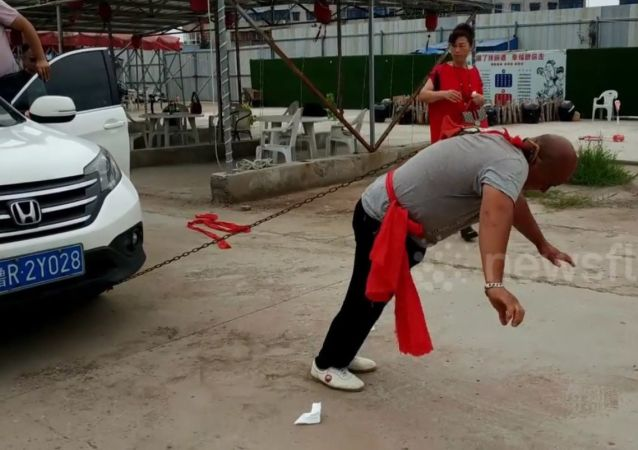 Kung Fu master moves two cars with an ear
