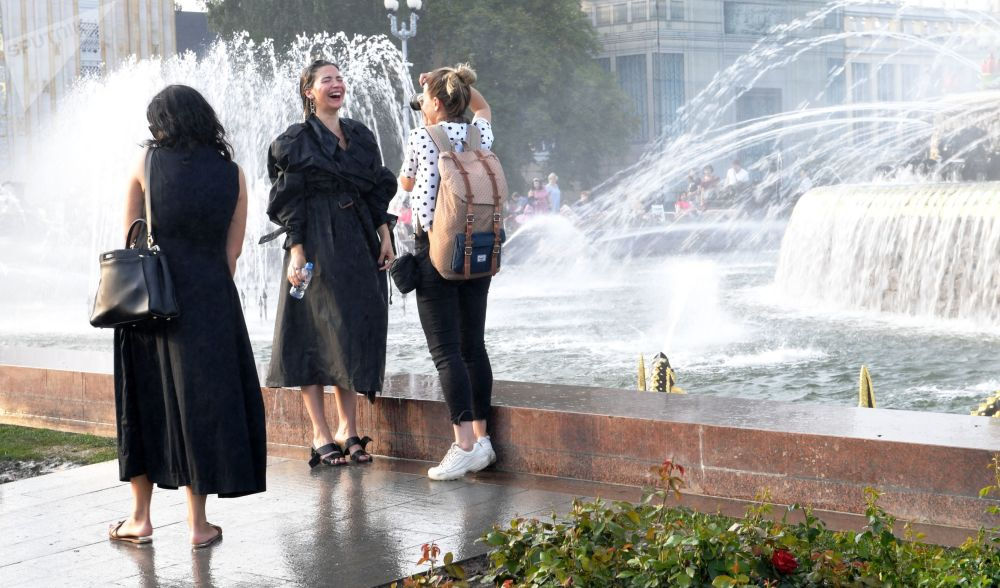 Girls taking pictures near the fountains of the Central Alley at VDNKH park in Moscow.