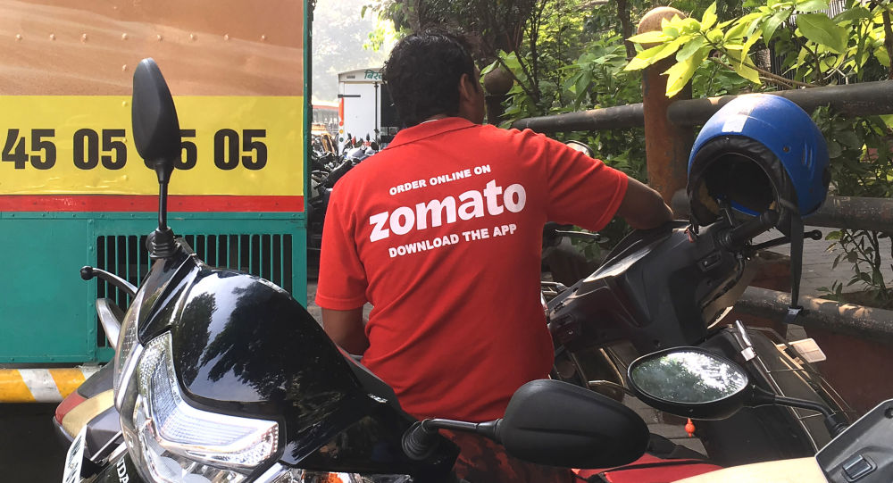 In this file photo taken on December 24, 2018 an Indian delivery man working with the food delivery app Zomato sits on his bike in Mumbai. - An Indian food service has sparked a national debate and set off a social media storm by defending a Muslim delivery driver who was rejected by a Hindu customer