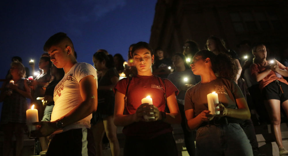 Samuel Lerma, Arzetta Hodges and Desiree Qunitana join mourners taking part in a vigil at El Paso High School after a mass shooting at a Walmart store in El Paso, Texas, 3 August 2019