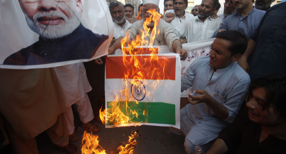 Pakistanis burn a representation of an Indian flag and a poster of Indian Prime Minster Narendra Modi during a protest to express support and solidarity with Indian Kashmiri people in their peaceful struggle for their right to self-determination, in Peshawar, Pakistan, Monday, Aug. 5, 2019