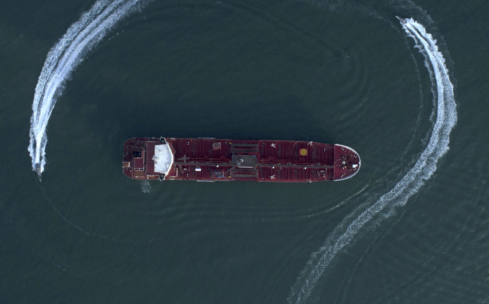 In this Sunday, July 21, 2019 photo, an aerial view shows a speedboat of Iran's Revolutionary Guard moving around the British-flagged oil tanker Stena Impero which was seized in the Strait of Hormuz on Friday by the Guard, in the Iranian port of Bandar Abbas