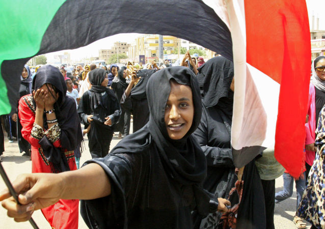 A Sudanese Demonstrater Waves National Flag