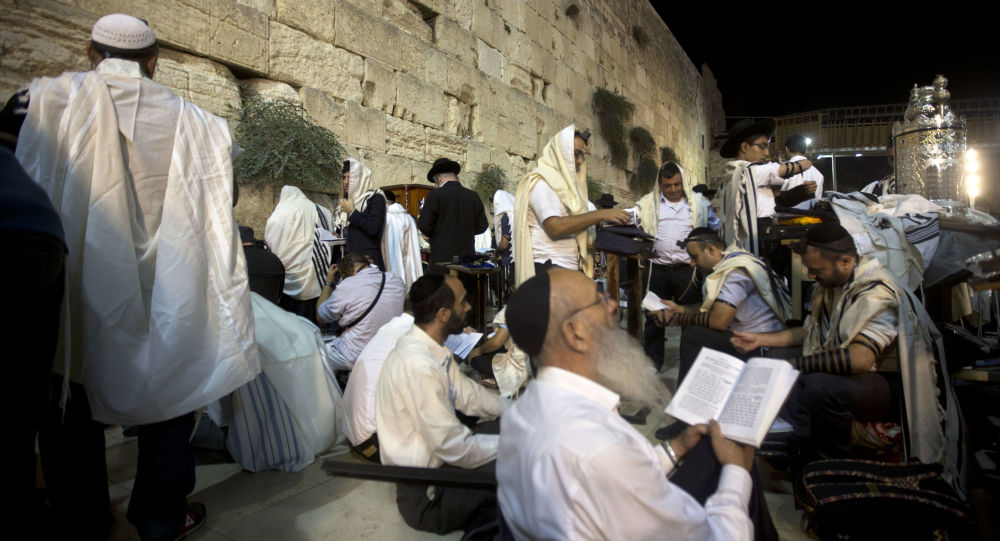 Jewish men pray during the mourning ritual of Tisha B'Av at the Western Wall, the holiest site where Jews can pray in Jerusalem's old city