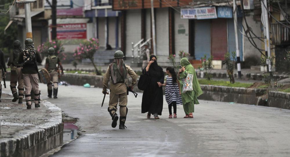 Kashmiris walks past Indian paramilitary soldiers patrolling a street in Srinagar, Indian controlled Kashmir, Saturday, Aug. 10, 2019