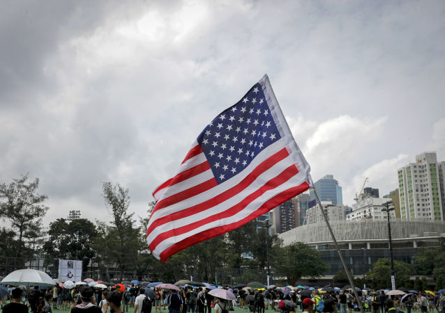 A U.S. flag flutters as people gather at Victoria Park to take part in an anti-extradition bill protest in Hong Kong, Sunday, Aug. 11, 2019. Protesters have begun gathering at the park in central Hong Kong for another day of demonstrations that have generally started peacefully but often ended in violent clashes with police.