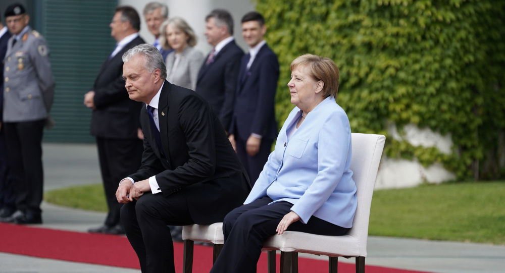 German Chancellor Angela Merkel and Lithuania's President Gitanas Nauseda sit down to listen to their national anthems during an official welcoming ceremony on August 14, 2019 at the Chancellery in Berlin